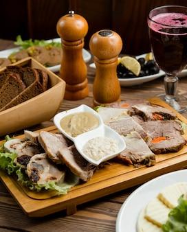 Стейк из мяса нарезанный и подается со специями, соусами, зеленым салатом и бокалом красного вина.