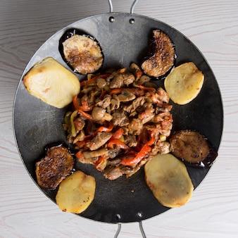 Азербайджанский сак ичи в черной сковороде со смешанными продуктами.