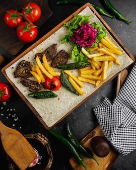 フライドポテトと野菜サラダの肉ステーキ。