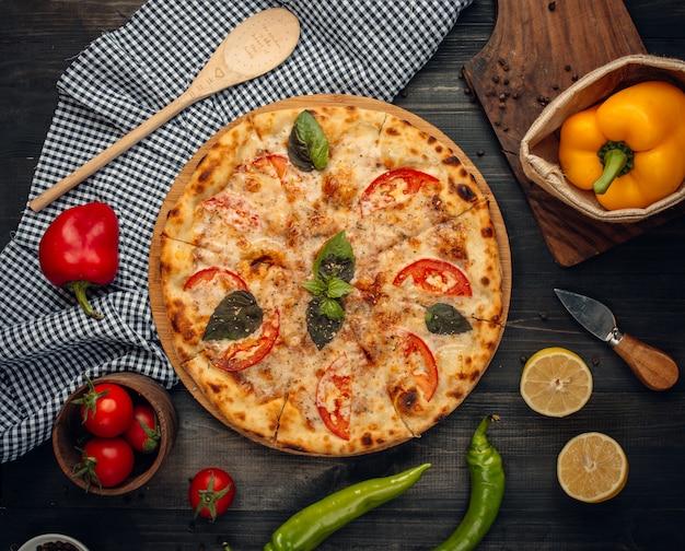 Пицца с зелеными ломтиками базилика и помидоров.