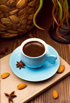 Свежий вкусный эспрессо. синяя чашка горячего кофе с миндалем и анисом