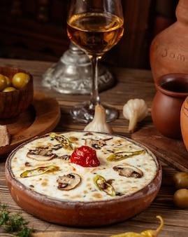 白ワインのグラスと陶器のボウルの中にクリームとキノコのスープ。