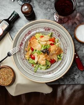Салат цезарь с крекерами и помидорами.