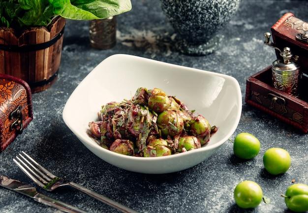 Салат с зелеными вишнями и мелко нарезанным луком.