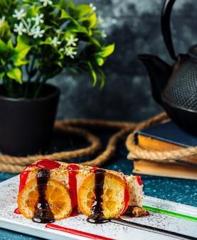 Чизкейк с дольками апельсина, шоколадом и красным сиропом.