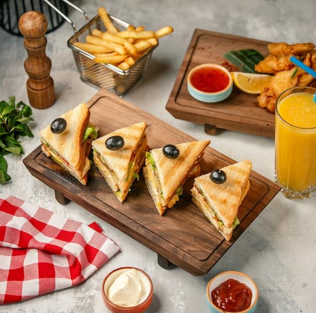 フライドポテトとオレンジジュースの木製ボード上のクラブサンドイッチ。