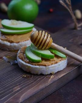 Хрустящий сэндвич с натуральным арахисовым маслом с рисовым хлебом, кусочками зеленого яблока и медом.