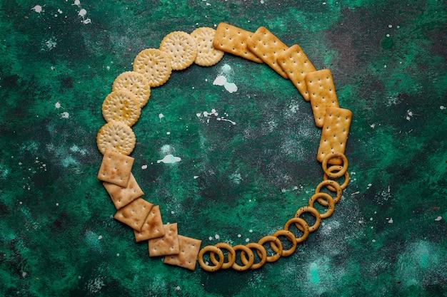 Ассортимент соленых крекеров снят с вершины на разноцветные с копией. микс соленой вечеринки