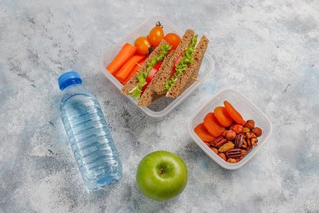 サンドイッチ、野菜、果物の白のお弁当。
