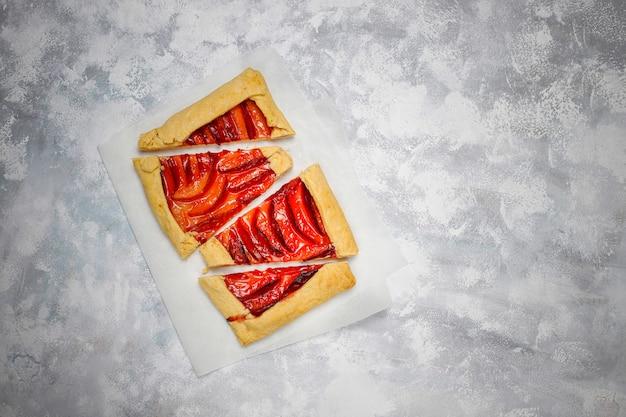 Свежий сливовый галетный пирог с сырой сливой на темном