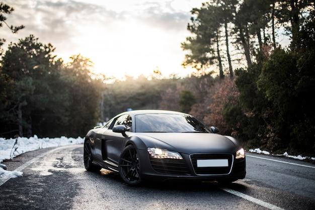 Хром черный спортивный автомобиль парковка с включенными передними огнями.