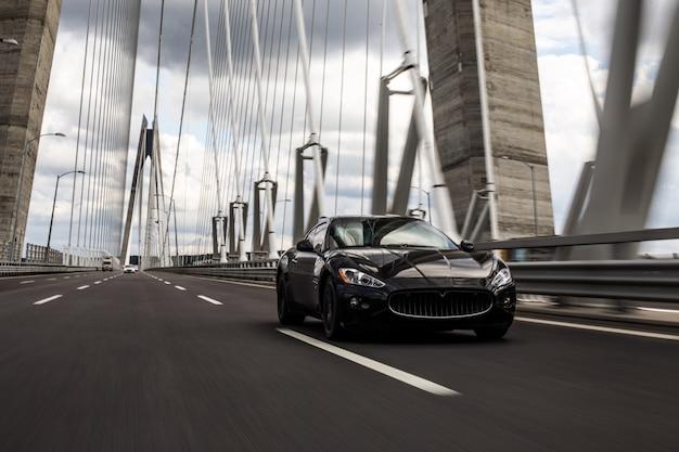 橋の道を走る黒いセダン車。