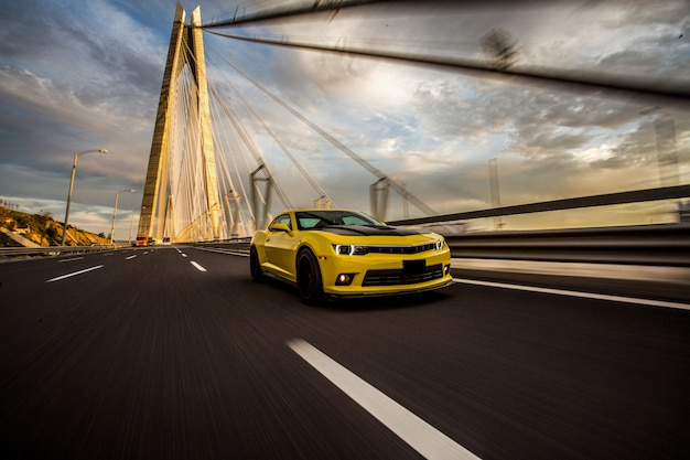 Желтый спортивный автомобиль с черным автотюнинга на мосту.