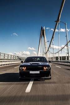 Вид спереди черной спортивной машины седана на мосту.
