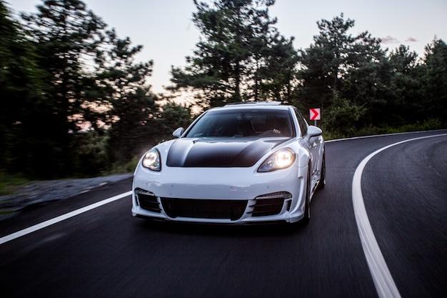 Белая спортивная машина с черным автонастройкой едет по дороге.