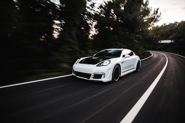 Белая спортивная машина с черным автонастройкой едет с высокой скоростью по дороге.