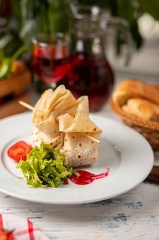 Фаршированный лаваш с салатом из помидоров и салата в белой тарелке
