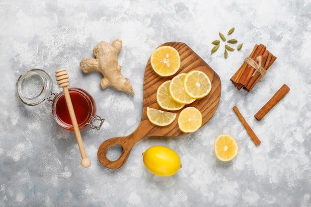Ломтики лимона на разделочной доске, палочки корицы, мед на бетоне. вид сверху, копия пространства