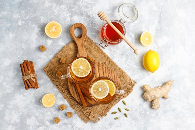 Чашка чая, коричневый сахар, мед и лимон на бетоне. вид сверху, копия пространства