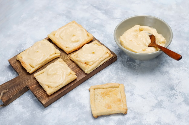 コンクリート、トップビューで生クリームと新鮮なおいしいパイ生地を作る