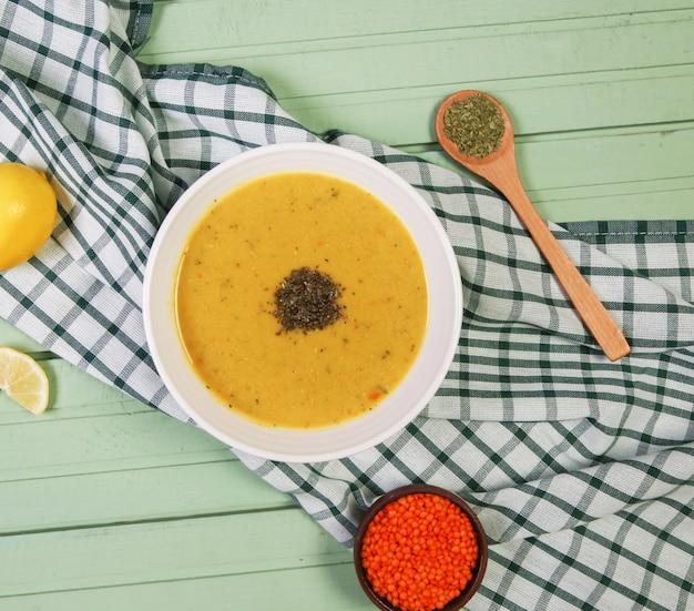 チェックテーブルクロスの白いボウルにハーブと赤レンズ豆のスープ。