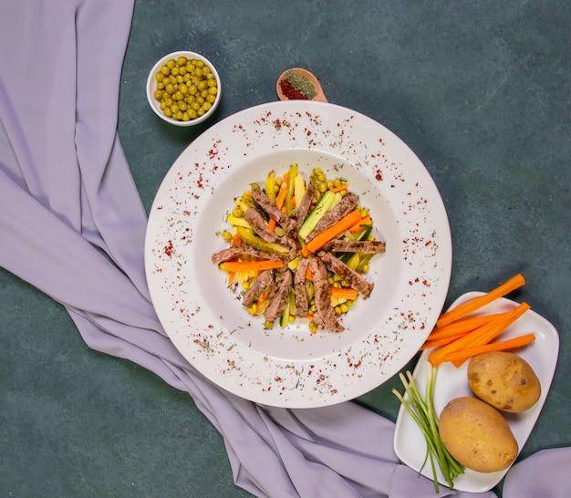 Обжаренный мясной салат с зеленой фасолью, картофелем и морковью.
