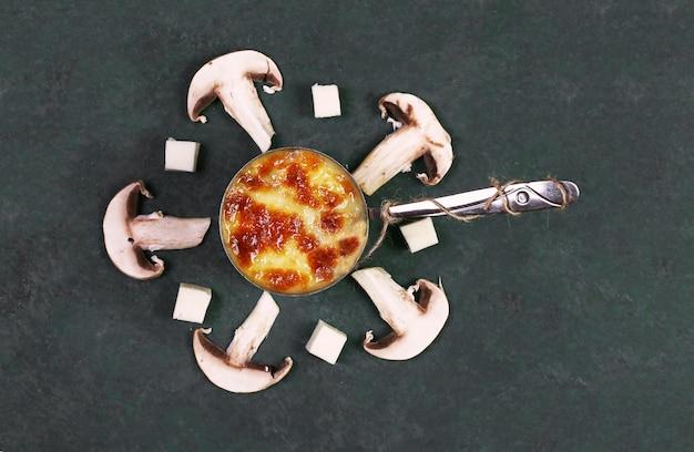 緑のテーブルの上のキノコとフライパンで溶かしたチーズ。
