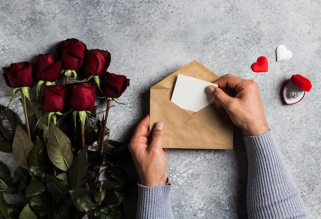 Рука человека дня святого валентина, держащая любовное письмо конверта с поздравительной открыткой
