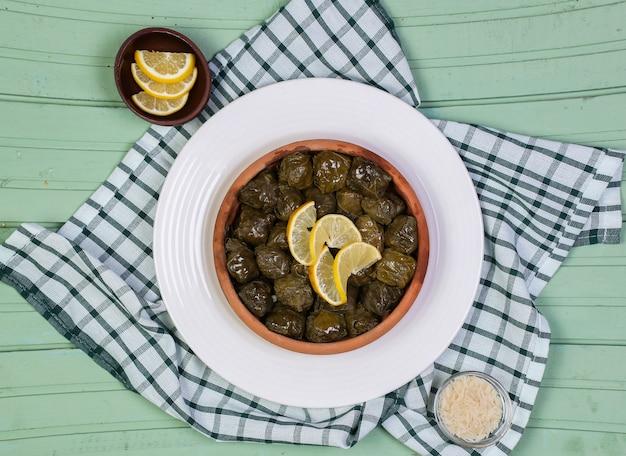 緑のテーブルの上の白い皿にレモンスライスと伝統的なヤルパグドルマシ。