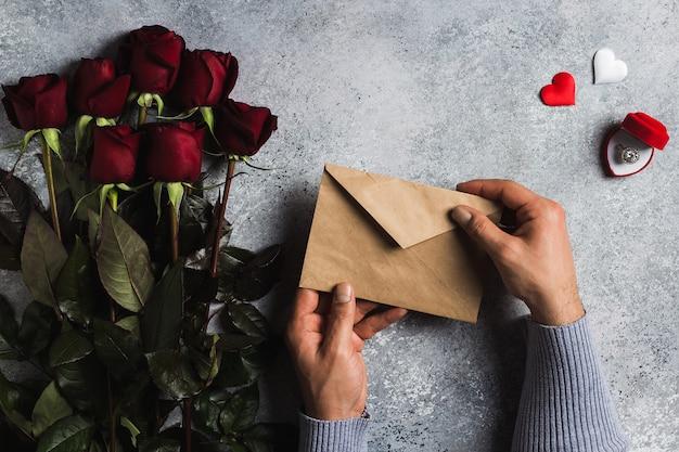 グリーティングカードと封筒ラブレターを持っているバレンタインデー男の手