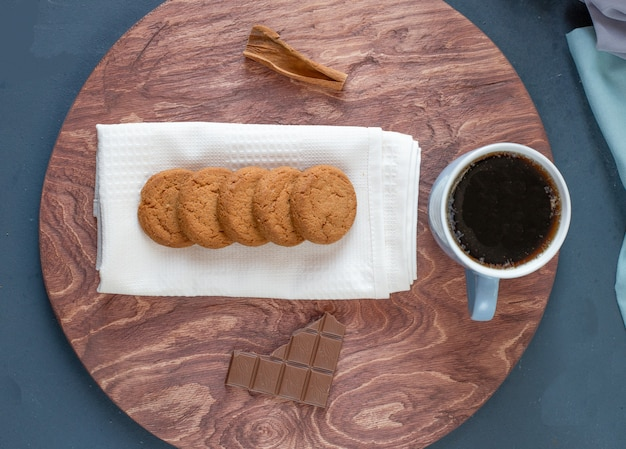 Овсяное печенье, чашка чая и шоколадная плитка на деревянной тарелке.