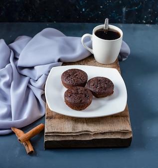 Шоколадные пирожные, палочки корицы и чашка кофе.