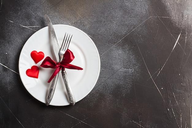 バレンタインの日のテーブルセッティングのロマンチックな夕食は私と結婚してプレートフォークナイフ