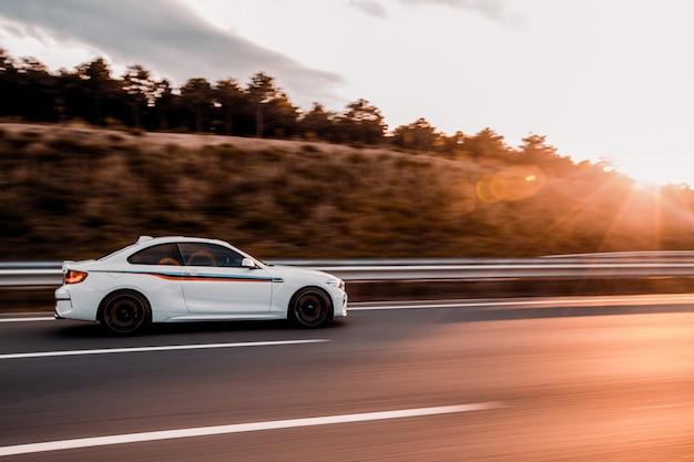 日没で道路を運転する白いクーペセダン