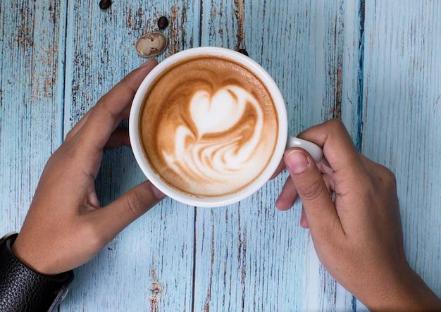 乳白色のコーヒーのカップを持っている人
