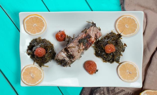 魚の切り身のグリル、グリーンサラダとレモンスライス