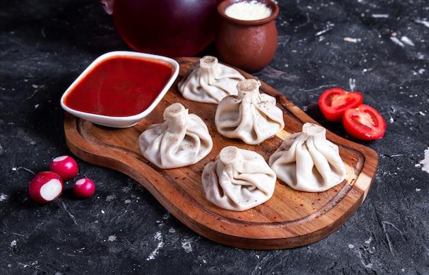 Китайские паровые булочки с красным соусом на деревянной доске