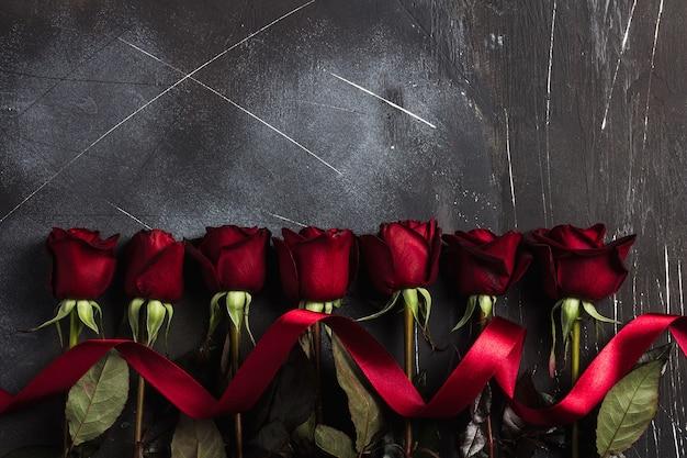 リボンのギフトの驚きとバレンタインの日女性の母親の日の赤いバラ