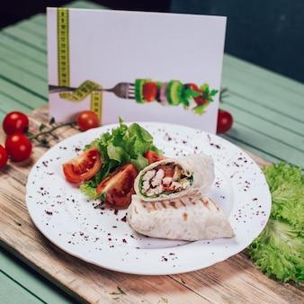 木の板に野菜サラダとアラビアの屋台シャウルマ。