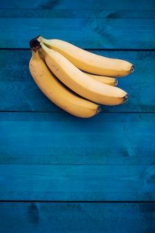 青い木製のテーブルの上の熱帯のバナナ