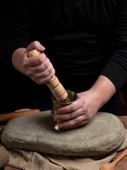 Человек в чёрной рубленой специи с помощью деревянной скалки на камне