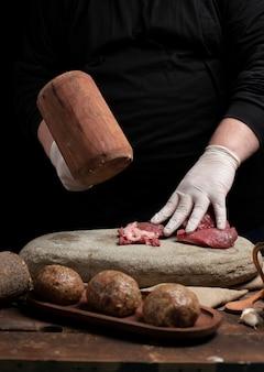 木製のハンマーで生肉を刻むシェフ