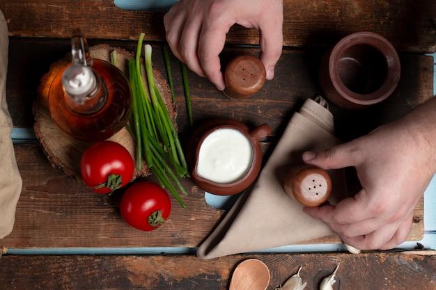 木製のテーブルにヨーグルトポット、トマト、ハーブ、オリーブボトル