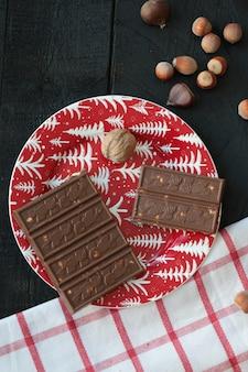 Шоколад и орехи в красную тарелку и на деревянный стол.