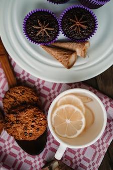 Чашка имбирного лимонного чая с печеньем и пирожными.