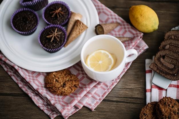 Чашка лимонно-имбирного чая с шоколадными пирожными.