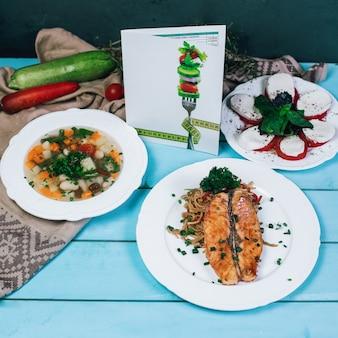 青い木製テーブルの上の野菜スープ、魚のフィレのグリル、モザレラのサラダ。
