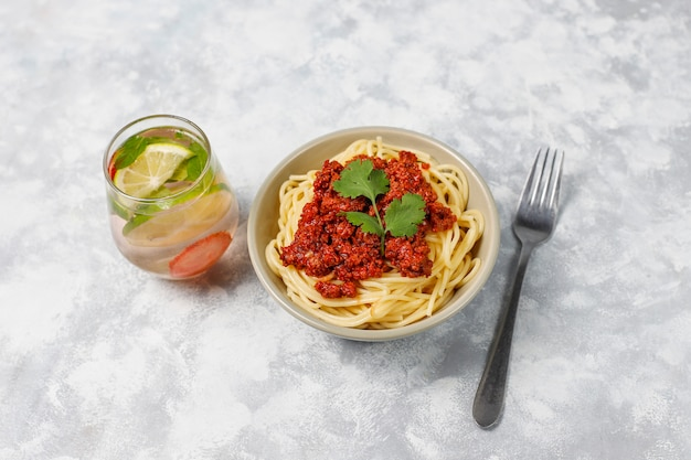 Спагетти болоньезе и лимонад на сером бетоне