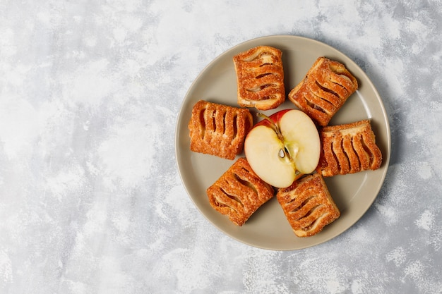 アップルジャムと軽いコンクリートの新鮮な赤いリンゴで満たされたパイ生地のクッキー