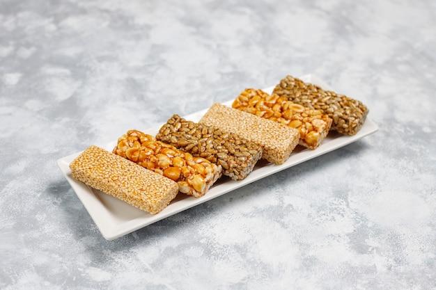 グラノーラバー。健康的な甘いデザートスナック。ゴマ、ピーナッツ、ひまわりのひまわり。ゴジナキはグルジアの国民食で、オリエンタルスイートです。コンクリートのトップビュー